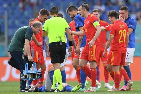 Нападающему сборной Италии Федерико Бернардески оказывают помощь после столкновения