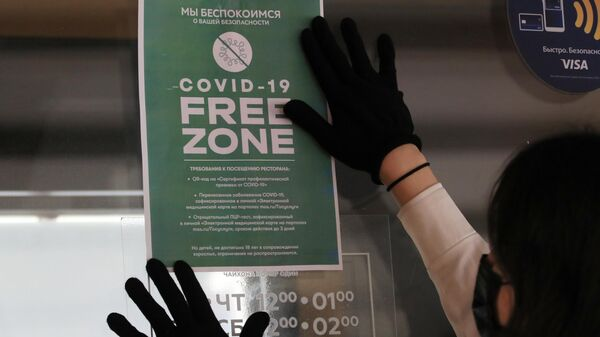 Сотрудник наклеивает объявление с информацией о требованиях к посещению ресторана Чайхона №1 на улице Дмитрия Ульянова в Москве