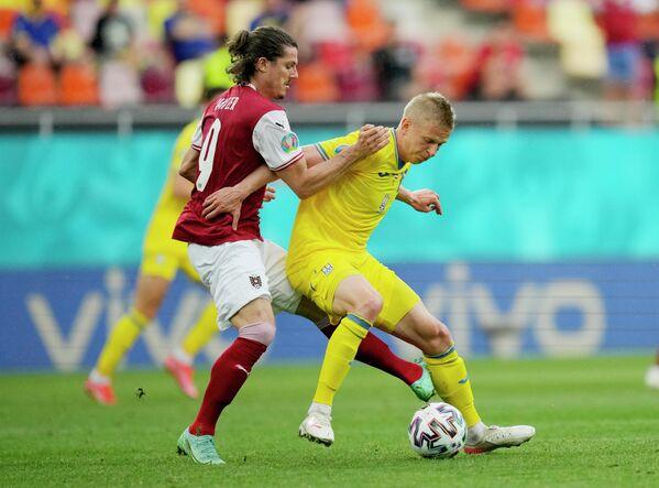 Полузащитник сборной Украины Александр Зинченко (справа) и нападающий сборной Австрии Кристоф Баумгартнер