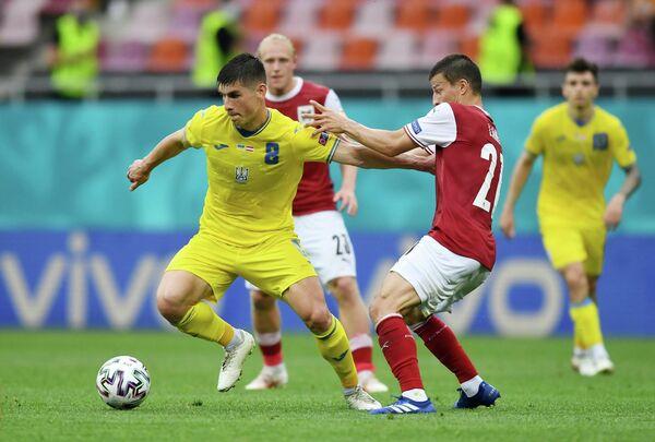 Полузащитник сборной Украины Руслан Малиновский и защитник сборной Австрии Штефан Лайнер (слева направо на первом плане)
