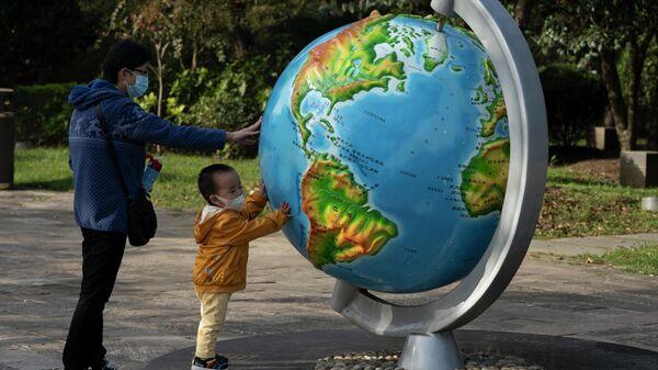 Женщина с ребенком у глобуса в парке в Ухани, Китай
