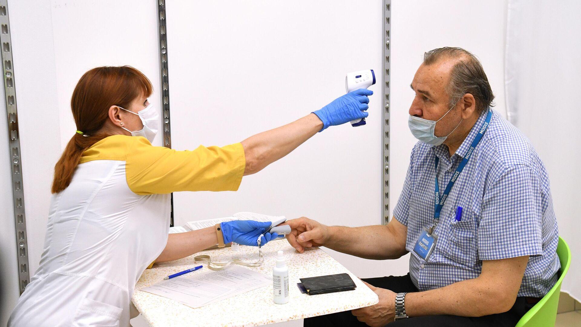 Медицинский работник измеряет температуру мужчине перед вакцинацией - РИА Новости, 1920, 24.07.2021