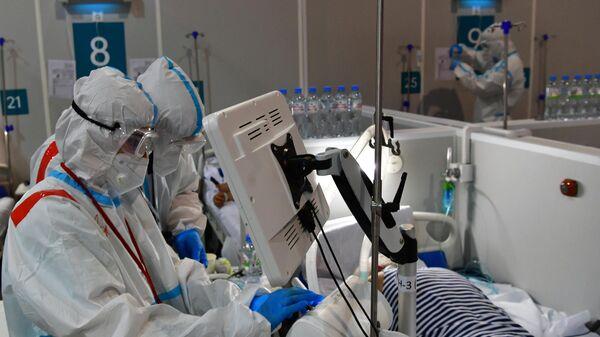 Медицинские работники и пациенты во временном госпитале для пациентов с COVID-19 в конгрессно-выставочном центре Сокольники в Москве
