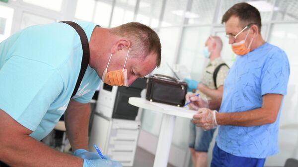 Мужчина заполняет анкету для вакцинации от covid-19 в павильоне Здоровая Москва в Парке Горького