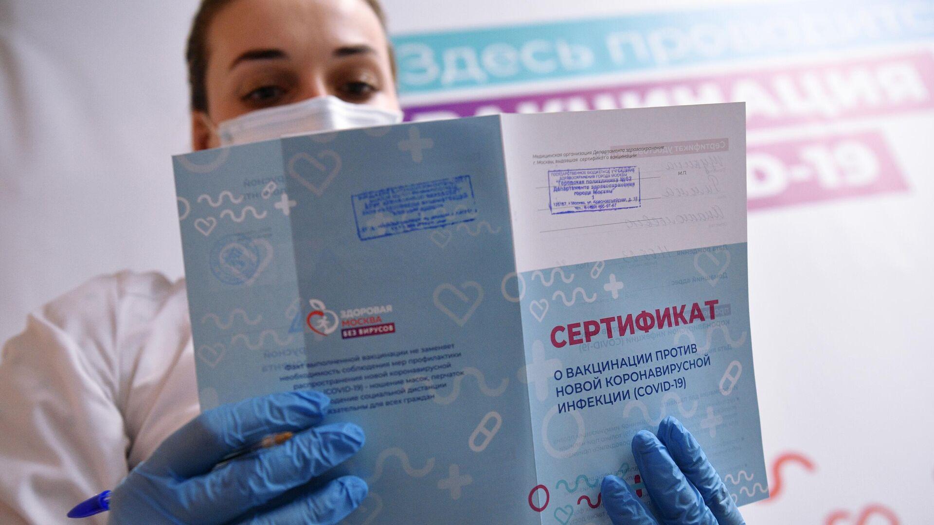 Медицинский работник держит в руках сертификат о вакцинации в мобильном пункте вакцинации от COVID-19 в торговом центре Арена Плаза в Москве - РИА Новости, 1920, 28.06.2021