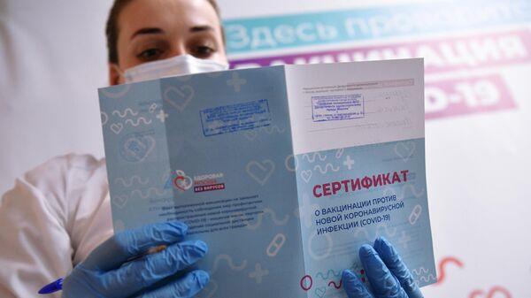Медицинский работник держит в руках сертификат о вакцинации в мобильном пункте вакцинации от COVID-19 в торговом центре Арена Плаза в Москве