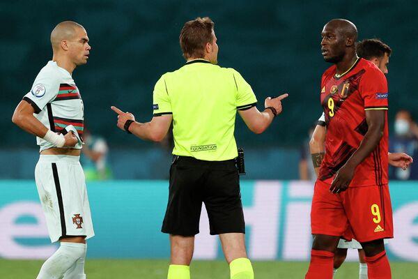 Арбитр Феликс Брых (в центре), защитник сборной Португалии Пепе (слева) и нападающий сборной Бельгии Ромелу Лукаку