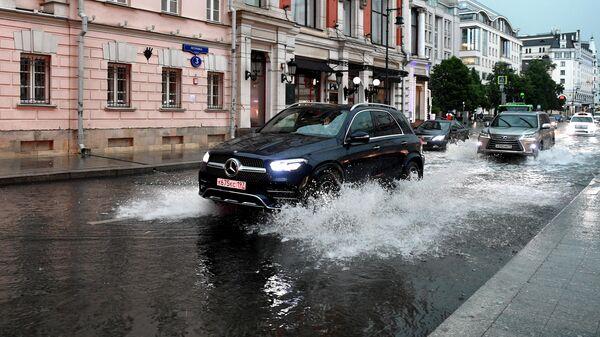 Автомобили едут по одной из улиц в Москве во время дождя