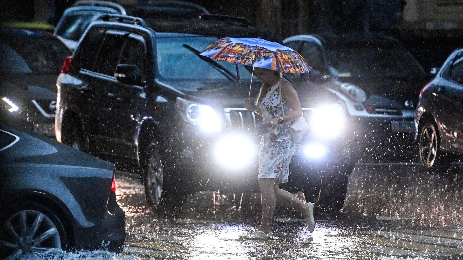 Девушка переходит дорогу на одной из улиц в Москве во время дождя - РИА Новости, 1920, 28.06.2021
