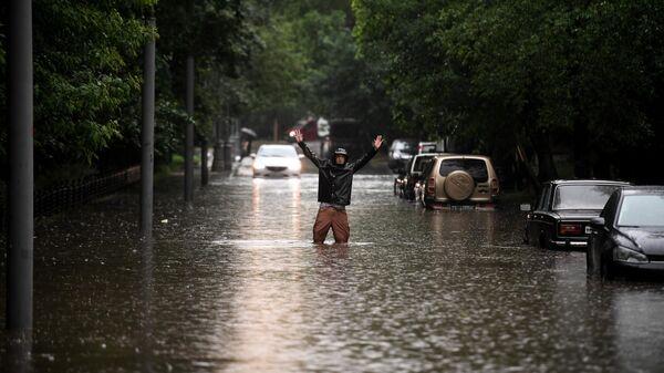 Мужчина одной из улиц в Москве во время дождя