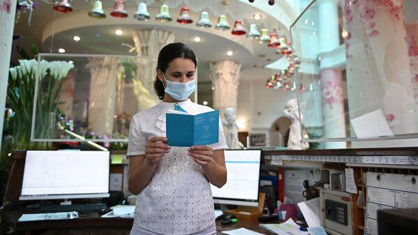Сотрудница санатория проверяет сертификат о вакцинации от CoVID-19 у гостьи