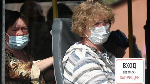 Пассажиры городского автобуса в защитных масках