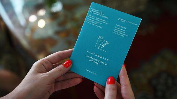 Отдыхающая держит в руках сертификат о вакцинации от CoVID-19 перед заселением в номер санатория Октябрьский в Краснодарском крае