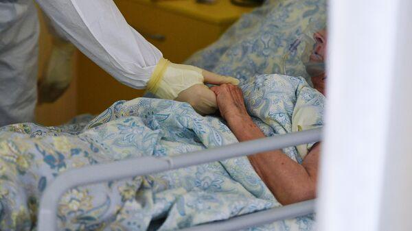 Медицинский работник возле кровати пациента