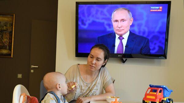 Женщина с ребенком смотрят трансляцию прямой линии с президентом РФ Владимиром Путиным