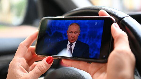 Женщина смотрит трансляцию прямой линии с президентом РФ Владимиром Путиным