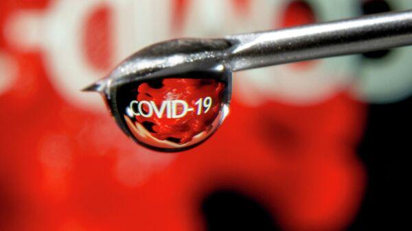 Слово COVID-19 в капле на игле шприца
