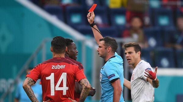 Главный арбитр Майкл Оливер показывает красную карточку полузащитнику сборной Швейцарии Ремо Фройлеру