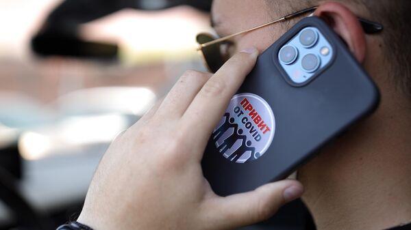 Наклейка с надписью Привит от COVID на смартфоне жителя, прошедшего вакцинацию от коронавируса в Краснодаре