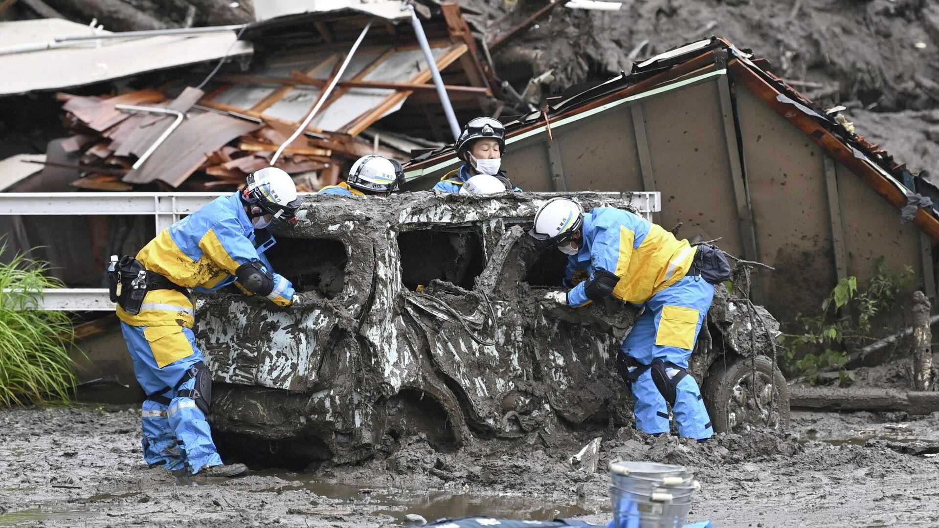Полицейские проводят поисково-спасательные работы на месте оползня, вызванного сильным дождем, в районе Идзусан в Атами, к западу от Токио, Япония - РИА Новости, 1920, 05.07.2021