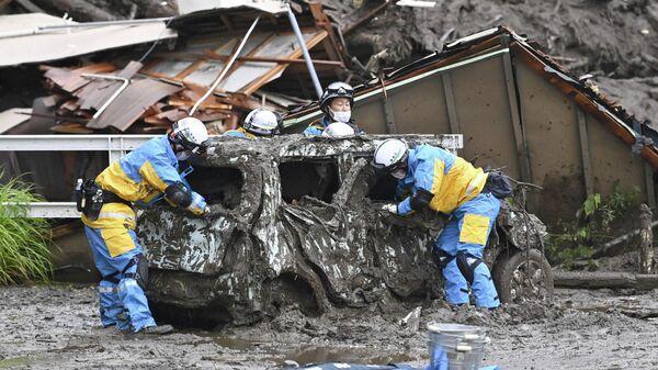 Полицейские проводят поисково-спасательные работы на месте оползня, вызванного сильным дождем, в районе Идзусан в Атами, к западу от Токио, Япония