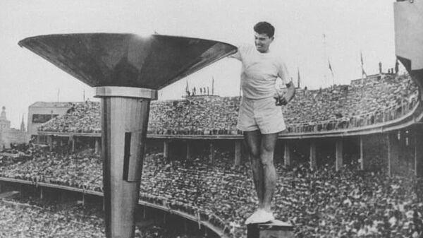 Австралийский легкоатлет Рон Кларк зажигает Олимпийский огонь перед началом Игр 1956 года в Мельбурне