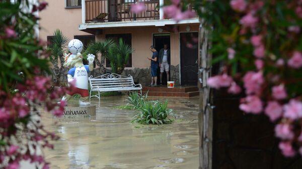 Гости во дворе подтопленной гостинцы неподалеку от реки Кудепста в Хостинском районе Сочи