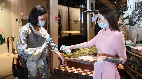 Хостес измеряет температуру у посетительницы перед посадкой за столик в ресторане BURO TSUM в Москве