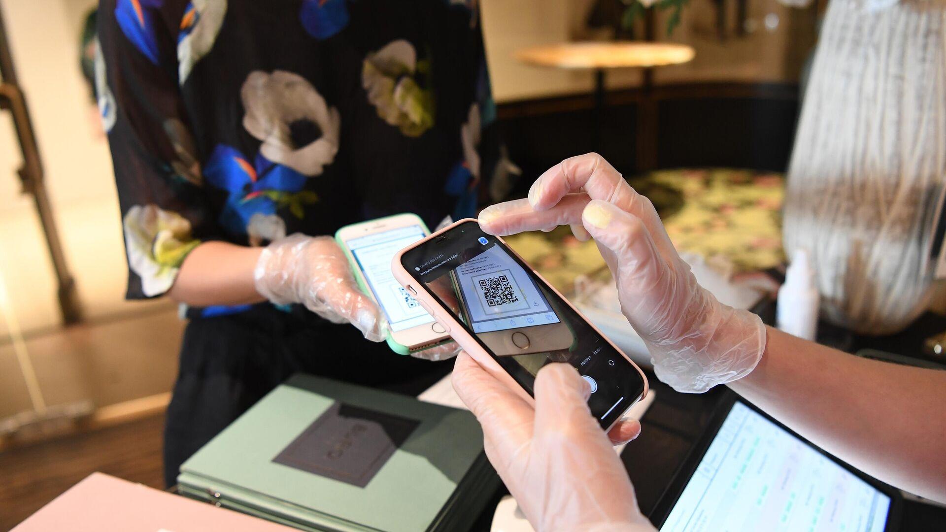 Хостес проверяет наличие и подлинность QR-кода у посетительницы перед посадкой за столик в ресторане BURO TSUM в Москве - РИА Новости, 1920, 19.07.2021