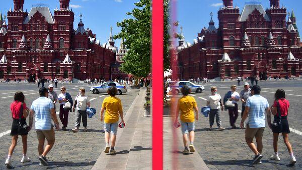 Люди у витрины ГУМа на Красной площади в Москве