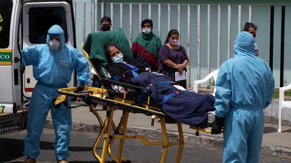 Медицинские работники и пациент с коронавирусной инфекцией возле больницы в Гватемале