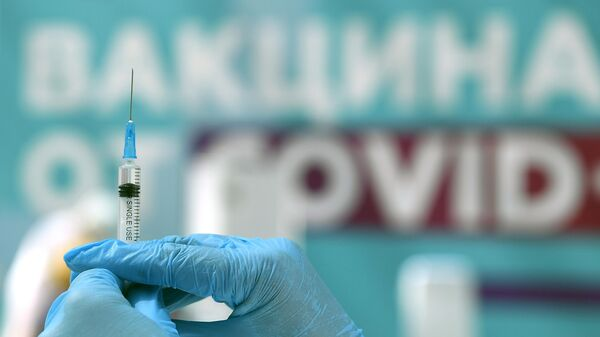 Медицинский сотрудник готовится сделать прививку посетителю в центре вакцинации от COVID-19 в Гостином дворе в Москве