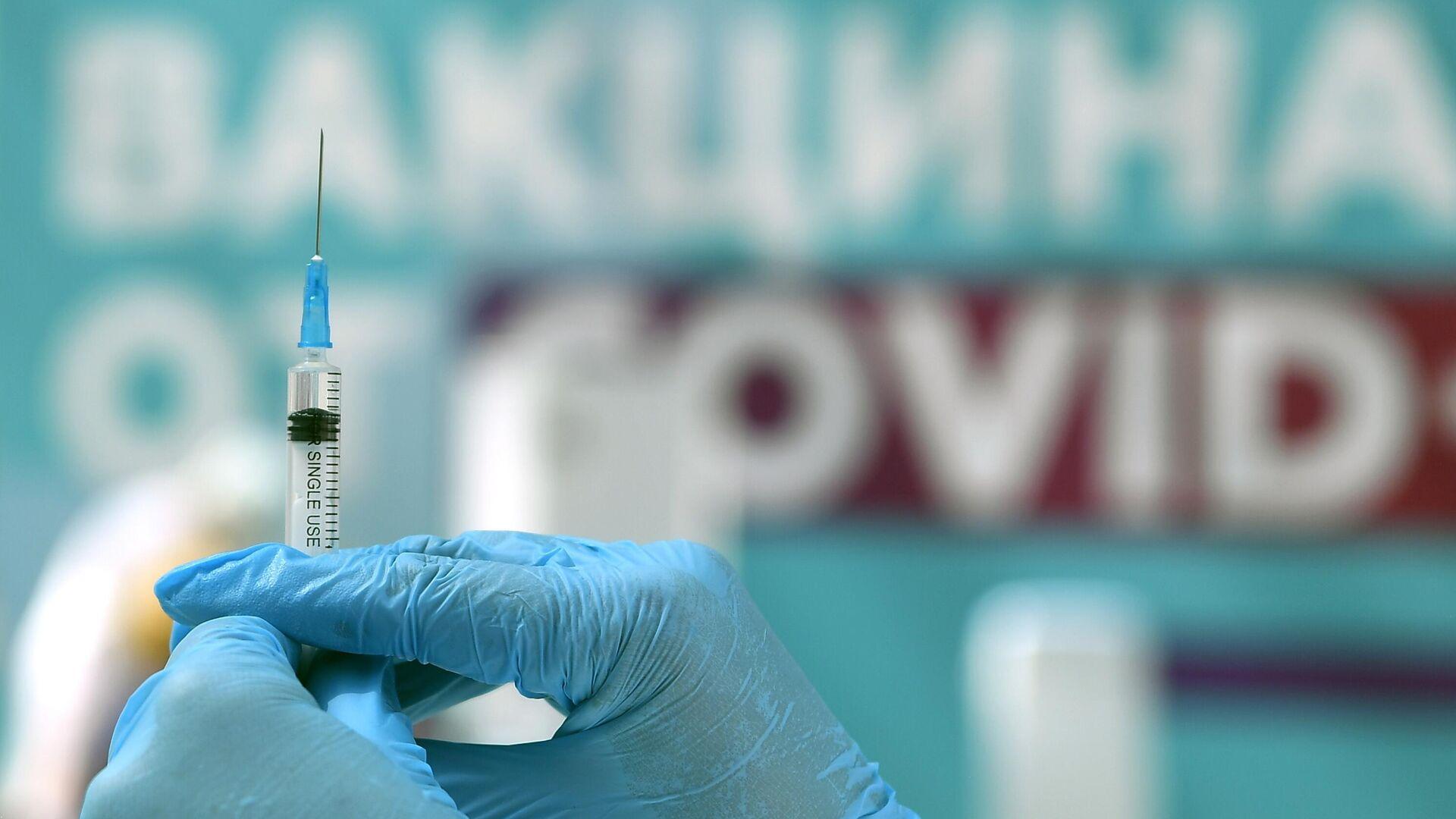 Медицинский сотрудник готовится сделать прививку посетителю в центре вакцинации от COVID-19 в Гостином дворе в Москве - РИА Новости, 1920, 20.07.2021