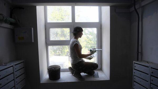 Маляр шпаклюет окно во время капитального ремонта в подъезде жилого дома