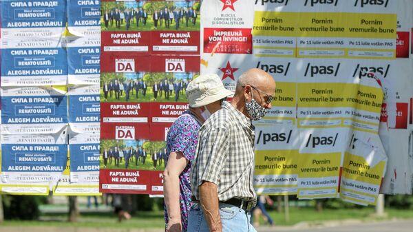 Люди проходят мимо избирательных плакатов накануне досрочных парламентских выборов в Кишиневе
