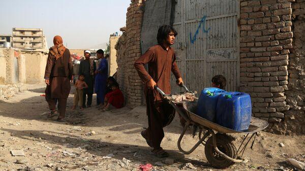Люди во временном лагере, пострадавшие в результате боевых действий, на одной из улиц Кабула