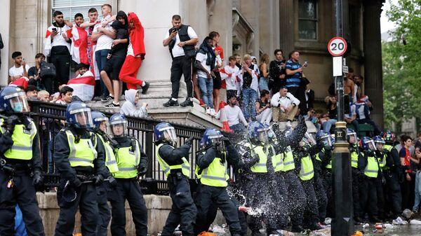 Полициейские и футбольные болельщики сборной Англии на Трафальгарской площади во время прямой трансляции финального футбольного матча ЕВРО-2020 между Англией и Италией в центре Лондона