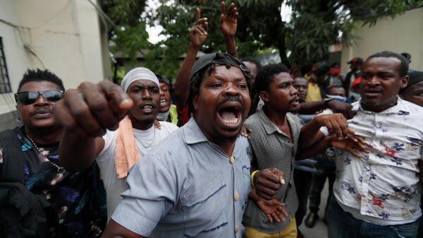 Сторонники бывшего сенатора Гаити Стивена Бенуа выступают перед зданием суда Порт-о-Пренсе
