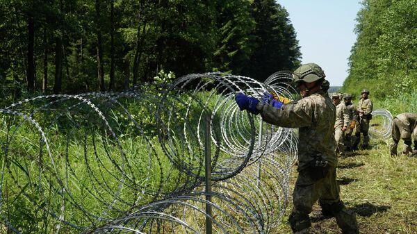 Солдаты литовской армии устанавливают забор из колючей проволоки на границе с Белоруссией в городе Друскининкай