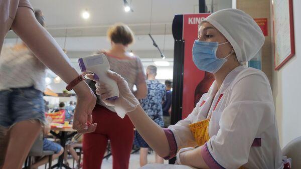 Работница кафе проверяет температуру у посетителей торгового центра