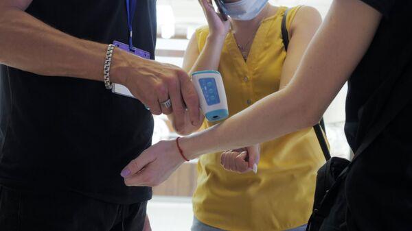 Сотрудник торгового центра в проверяет температуру у посетителей
