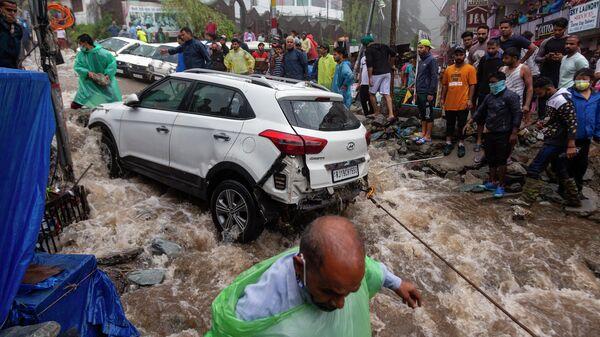 Люди пытаются вытащить автомобиль после наводнения в Индии