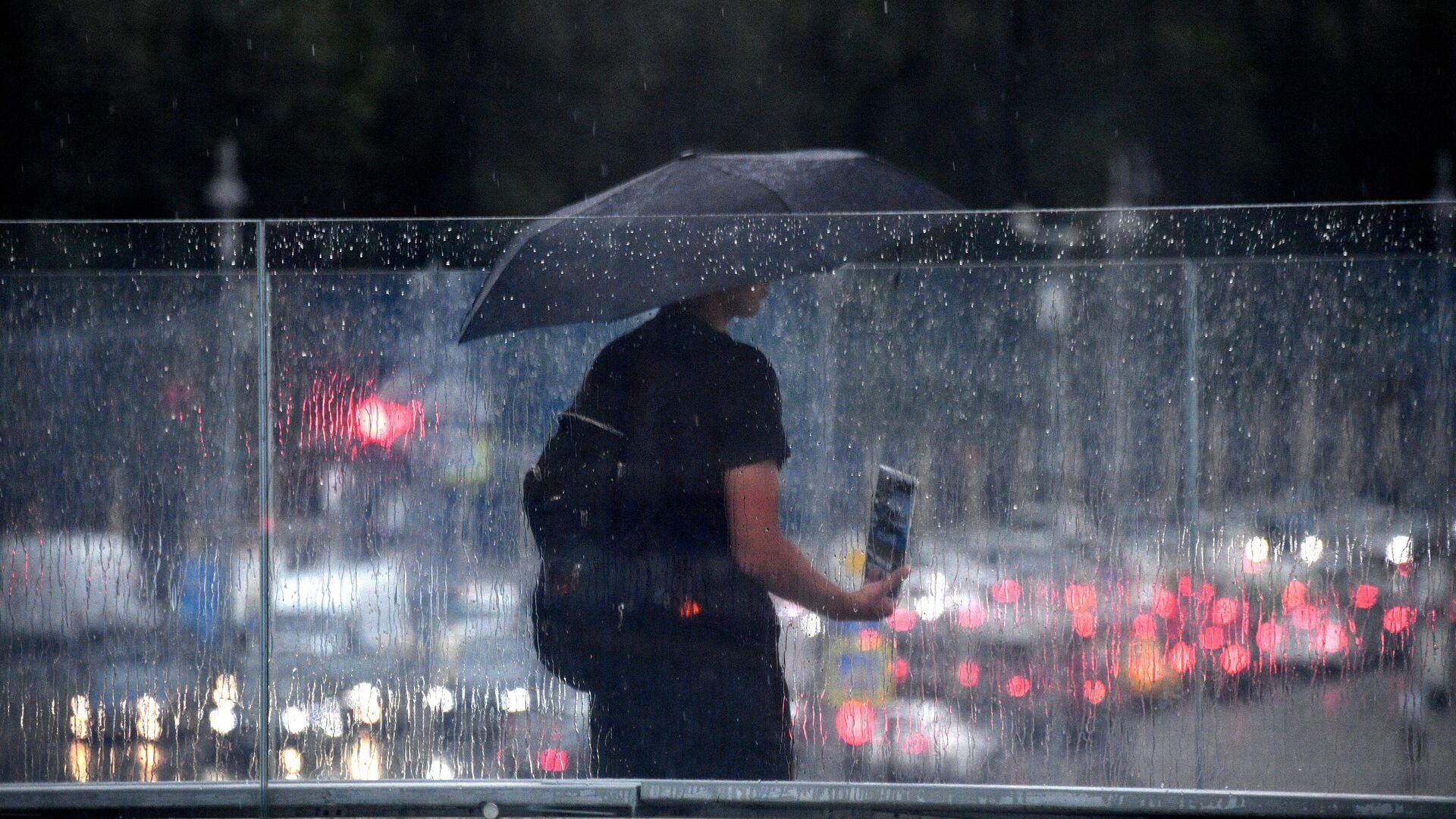 Мужчина под зонтом на одной из улиц в Москве - РИА Новости, 1920, 06.08.2021