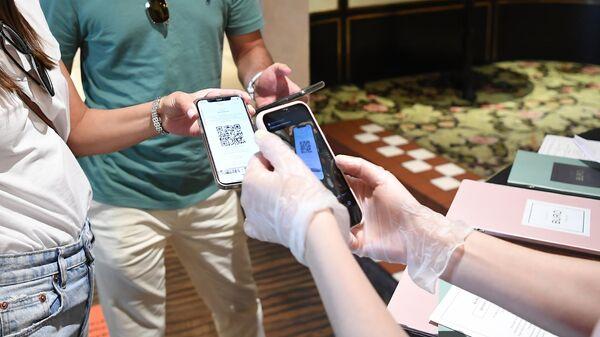 Хостес проверяет наличие и подлинность QR-кода у посетителей