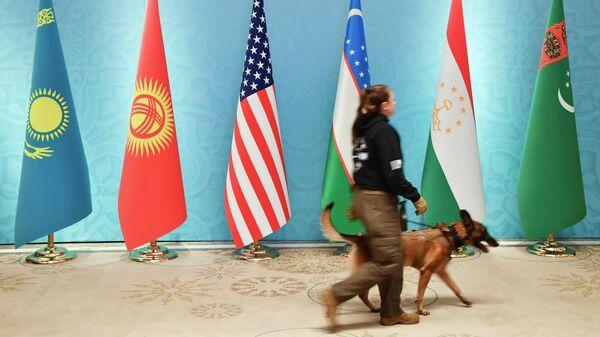 Офицер службы безопасности проходит мимо национальных флагов Казахстана, Кыргызстана, США, Узбекистана, Таджикистана и Туркменистана перед встречей в Ташкенте