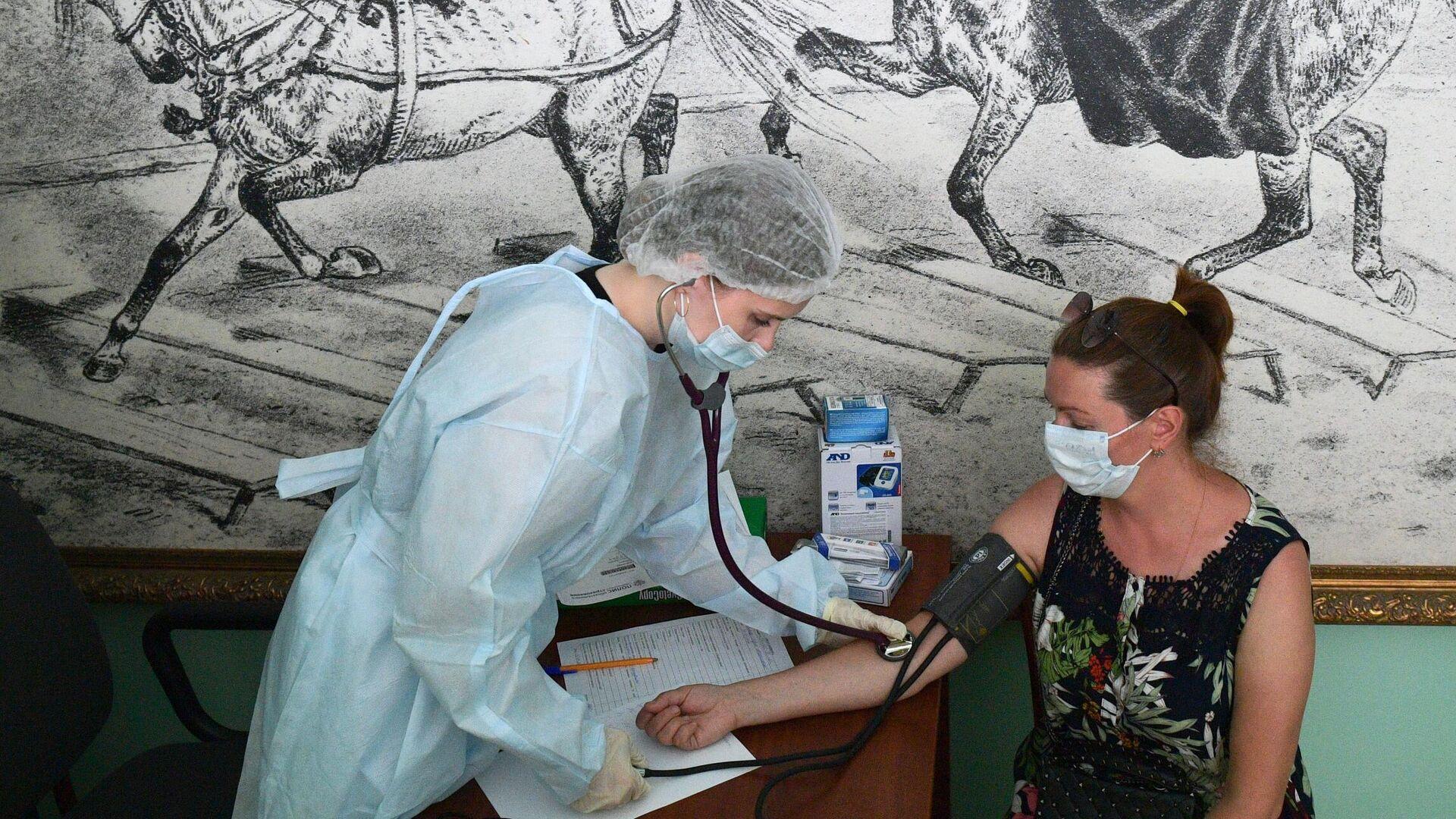 Медицинский сотрудник измеряет давление женщине перед вакцинацией от COVID-19 в Санкт-Петербурге - РИА Новости, 1920, 20.07.2021