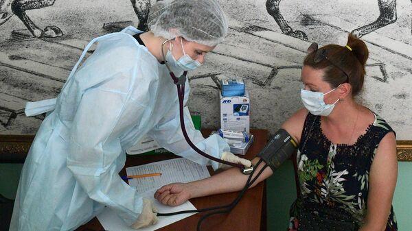 Медицинский сотрудник измеряет давление женщине перед вакцинацией от COVID-19 в Санкт-Петербурге