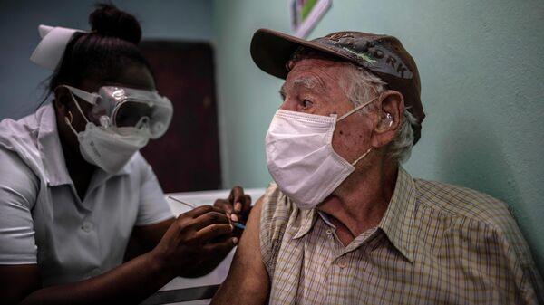 Медицинский работник и пациент во время вакцинации кубинской вакциной Abdala в Гаване