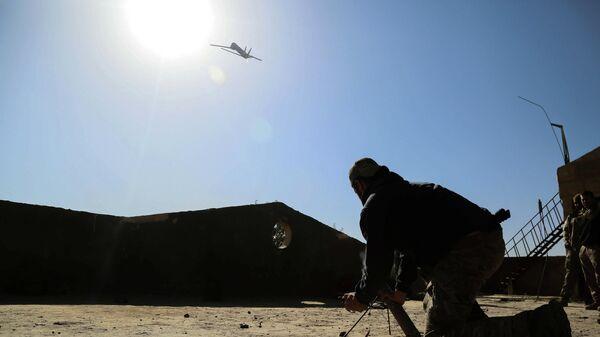 Американский военный запускает беспилотный летательный аппарат в Сирии