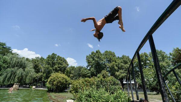 Мальчик прыгает в воду в жаркий день в Центральном парке культуры и отдыха Симферополя